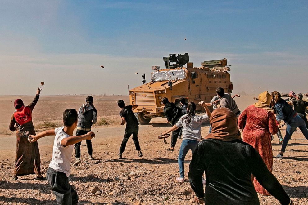 PHOTO: Syrians throw stones towards Turkish military vehicles during a Turkish-Russian army patrol near the town of Darbasiyah in Syrias northeastern Hasakeh province along the Syria-Turkey border on Nov. 11, 2019.