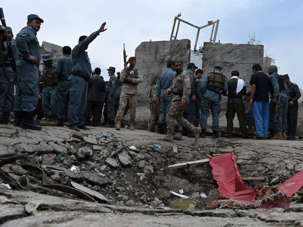PHOTO: Afghan security personnel stand at the scene of a suicide attack by Taliban militants on the Afghan parliament building in Kabul on June 22, 2015.