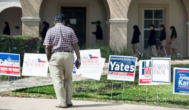 PHOTO: A voter stops to look at primary election signs outside the polling place at St. Annes Catholic Church on Tuesday, March 6, 2018, in Houston.