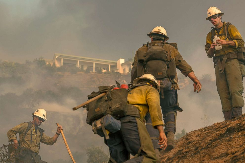 PHOTO: A Hot Shot crew climbs a hill while cutting a line among homes at the Thomas Fire, Dec. 16, 2017, in Montecito, Calif.