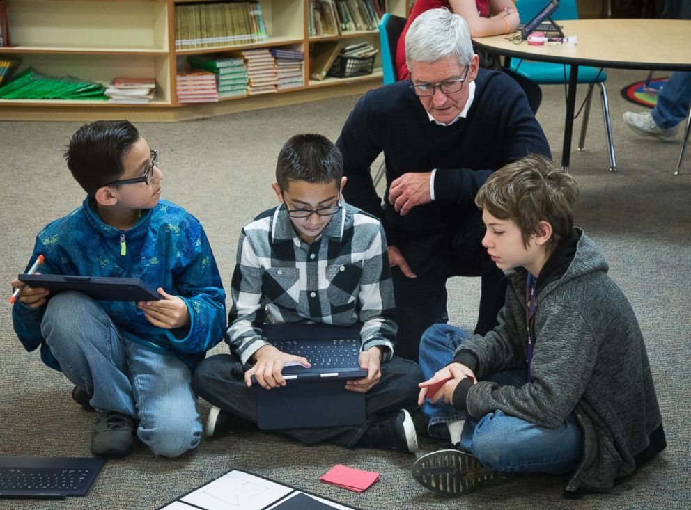 Apple CEO Tim Cook talks with Marco Aranjo, left, Fernny Flores, and Hunter Lansdell, about the coding they've done as they play a self-programmed game of Battleship at Wilder Elementary School, Nov. 27, 2018, in Boise, Idaho.