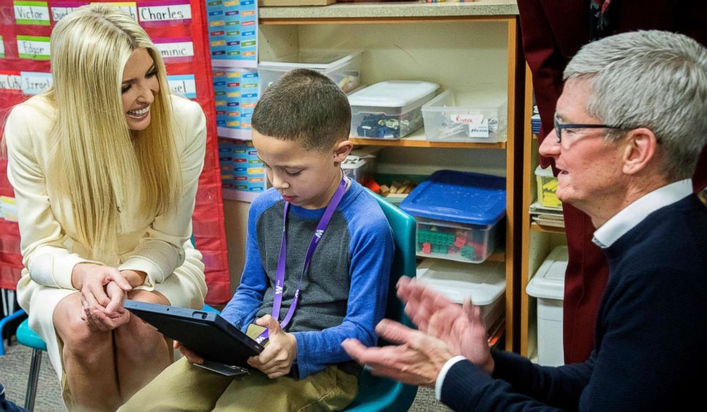 Apple CEO Tim Cook, right, and Ivanka Trump, left, daughter and adviser to President Donald Trump, watch as first-grader Salvador Esparza shows them work he's doing on a video during a visit to Wilder Elementary School, Nov. 27, 2018, in Boise, Idaho.