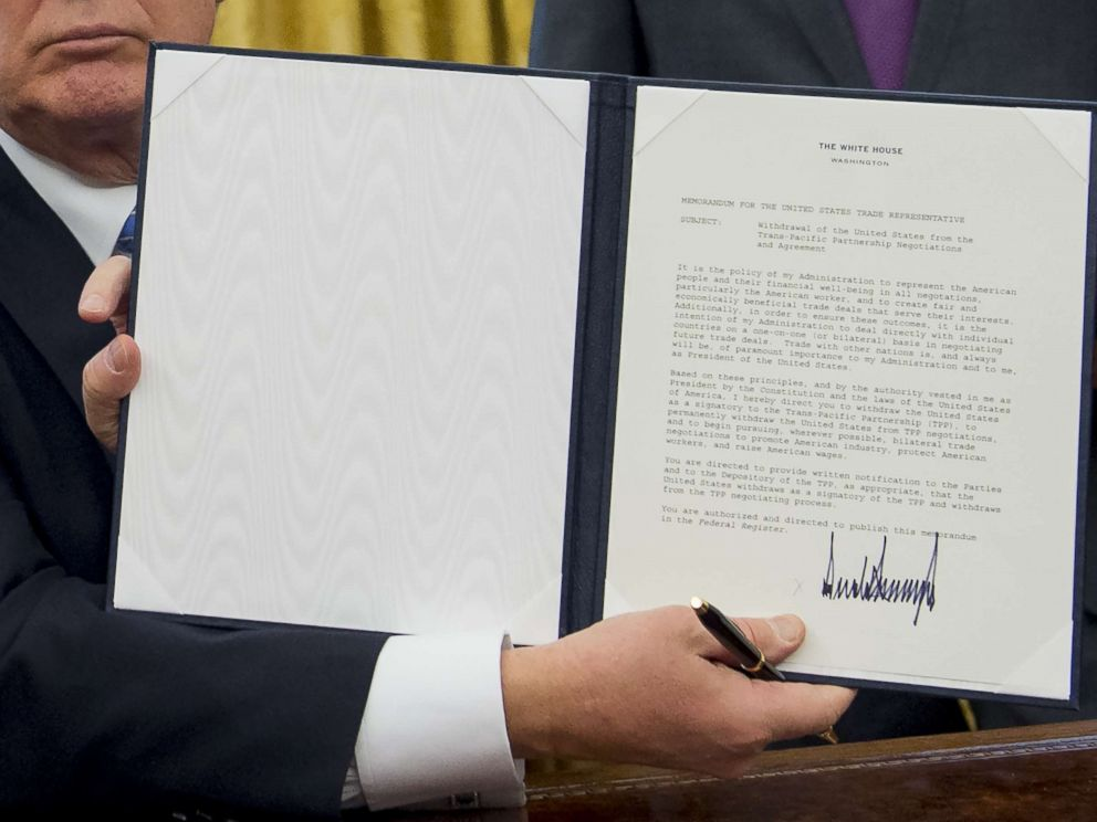 PHOTO: President Donald Trump holds up an executive order withdrawing the US from the Trans-Pacific Partnership after signing it in the Oval Office of the White House in Washington, DC, Jan. 23, 2017.