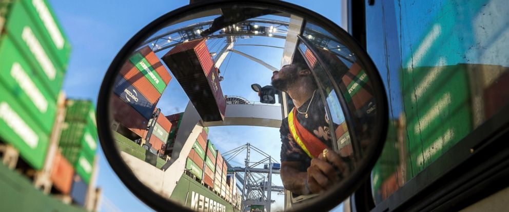 In this June 19 photo, a truck driver waits for a shipping container to clear his trailer at the Port of Savannah in Georgia. The U.S. has imposed 25 percent duties on $34 billion in Chinese products.