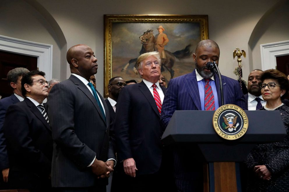 PHOTO: Donte Hickman, pastor at Southern Baptist Church in Baltimore, speaks as President Donald Trump and Sen. tim Scott, R-S.C., listen before Trump signs an executive order establishing the White House Opportunity and Revitalization Council.