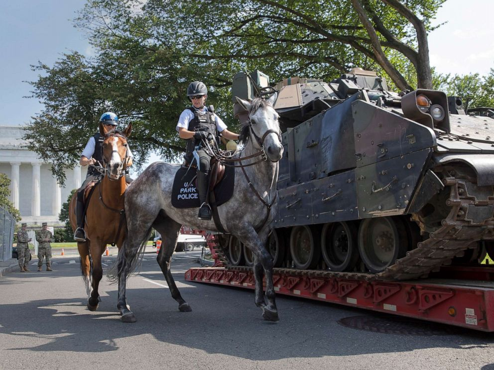 PHOTO: Mounted US Park Police pass by an armored Bradley Fighting Vehicle near the Lincoln Memorial as preparations continue for Independence Day celebrations on the National Mall in Washington, D.C., July 3, 2019.