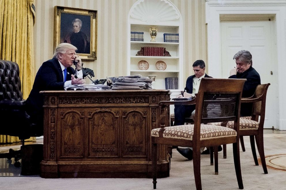 PHOTO: President Donald Trump, left, speaks on the phone while National Security Advisor Michael Flynn, Chief Strategist Steve Bannon listen, in the Oval Office, Jan. 28, 2017.