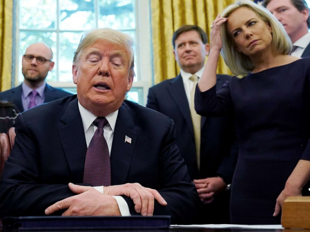 PHOTO: President Donald Trump talks to reporters as Department of Homeland Security Secretary Kirstjen Nielsen, right, looks on at a signing ceremony in the Oval Office of the White House, Nov. 16, 2018.