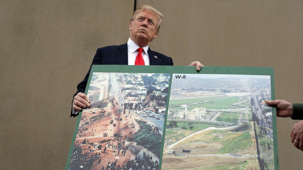 President Donald Trump holds an image of the border area as he speaks during a tour to review border wall prototypes, March 13, 2018, in San Diego.