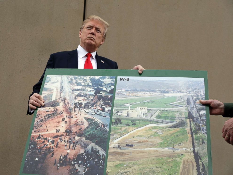 PHOTO: President Donald Trump holds an image of the border area as he speaks during a tour to review border wall prototypes, March 13, 2018, in San Diego.