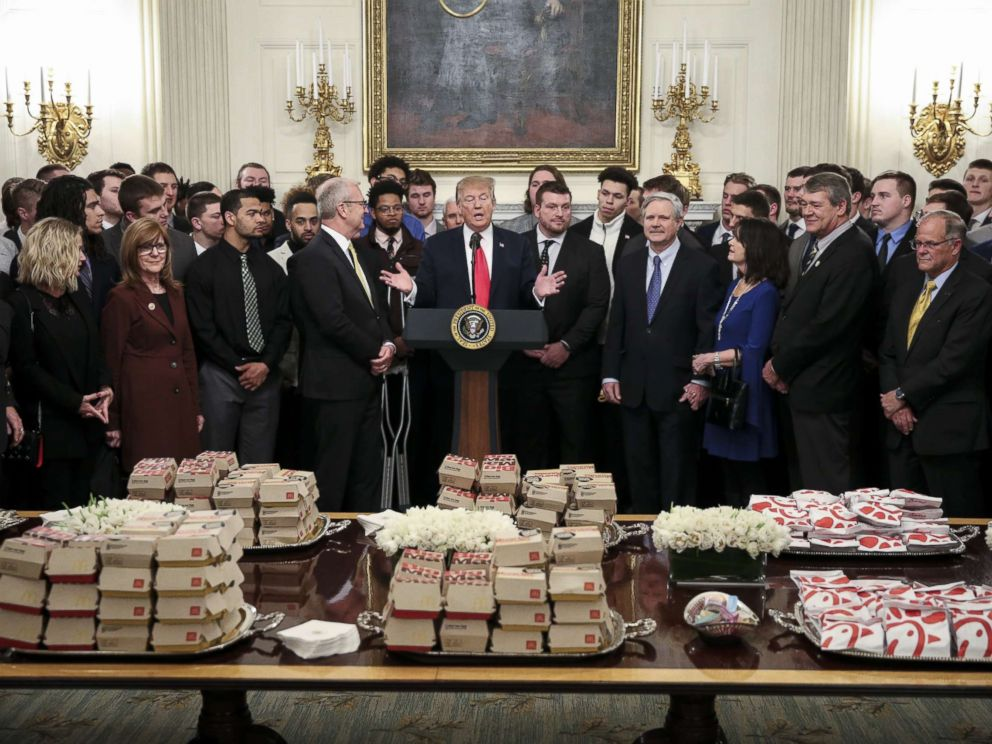 PHOTO: President Donald Trump speaks behind a table full of McDonalds hamburgers as he welcomes the 2018 Football Division I FCS champs North Dakota State Bison in the Diplomatic Room of the White House, March 4, 2019.