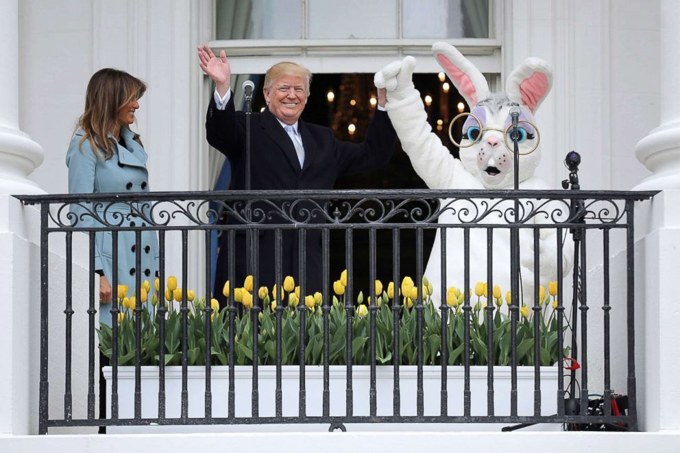 PHOTO: President Donald Trump and first lady Melania Trump walk out onto the Truman Balcony with a person in an Easter Bunny costume during the 140th annual Easter Egg Roll at the White House, April 2, 2018 in Washington, DC.