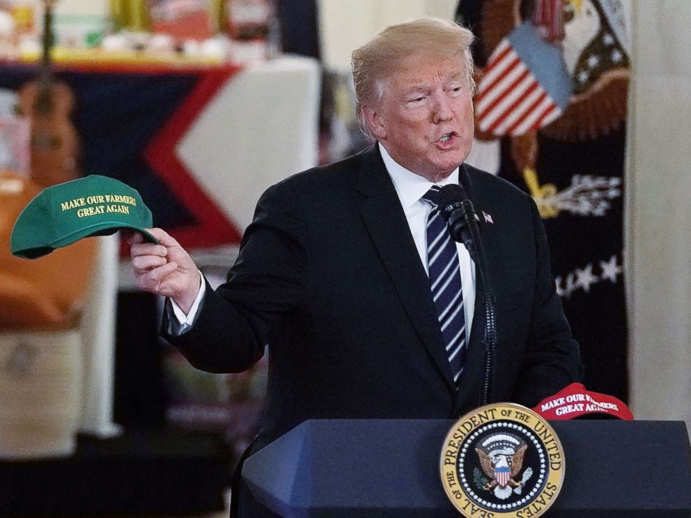 PHOTO: President Donald Trump holds up a Make Our Farmers Great Again hat as he speaks during the 2018 Made in America Product Showcase event, July 23, 2018, in the Cross Hall of the White House in Washington, D.C.