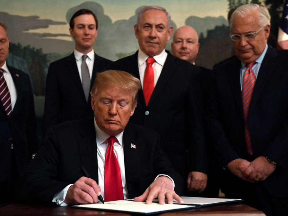 PHOTO: President Donald Trump, front, signs a proclamation in the Diplomatic Reception Room at the White House in Washington, Monday, March 25, 2019. Trump signed an official proclamation formally recognizing Israels sovereignty over the Golan Heights.