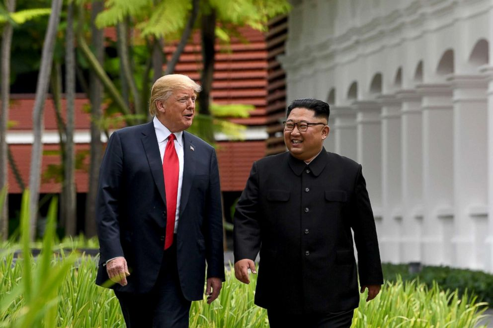 PHOTO: North Koreas leader Kim Jong Un walks with President Donald Trump, left, during a break in talks at their historic US-North Korea summit at the Capella Hotel on Sentosa island in Singapore, June 12, 2018.