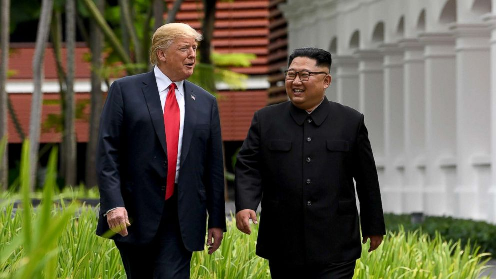 North Korea's leader Kim Jong Un walks with President Donald Trump, left, during a break in talks at their historic US-North Korea summit at the Capella Hotel on Sentosa island in Singapore, June 12, 2018.