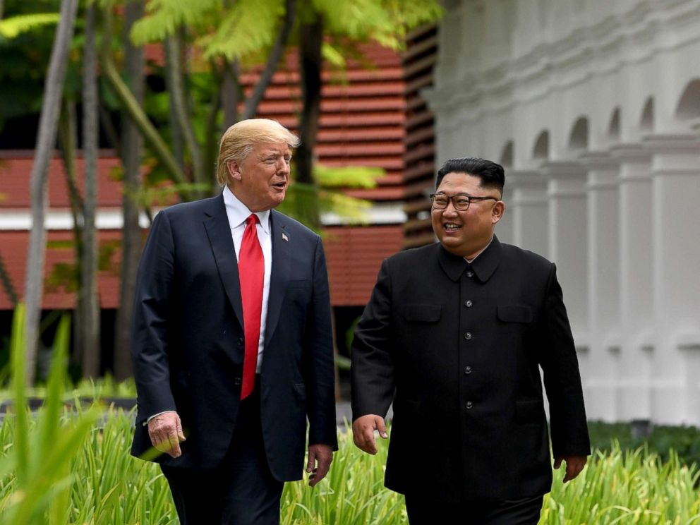 PHOTO: North Koreas leader Kim Jong Un walks with President Donald Trump during a break in talks at their historic U.S.-North Korea summit in Singapore, June 12, 2018.