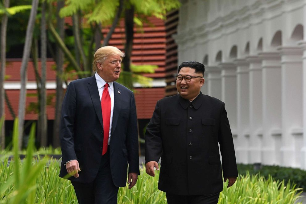 PHOTO: North Koreas leader Kim Jong Un, right, walks with President Donald Trump during a break in talks at their historic US-North Korea summit, at the Capella Hotel on Sentosa island in Singapore.