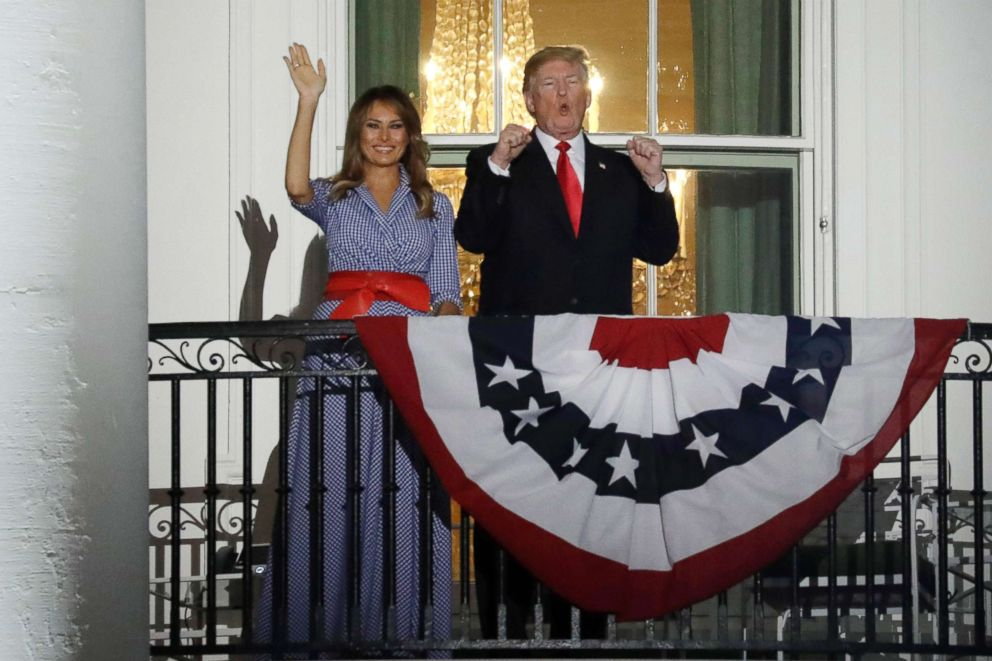 PHOTO: President Donald Trump, right, gestures as First Lady Melania Trump waves from a balcony of the White House during a fireworks display in Washington, D.C., July 4, 2018.