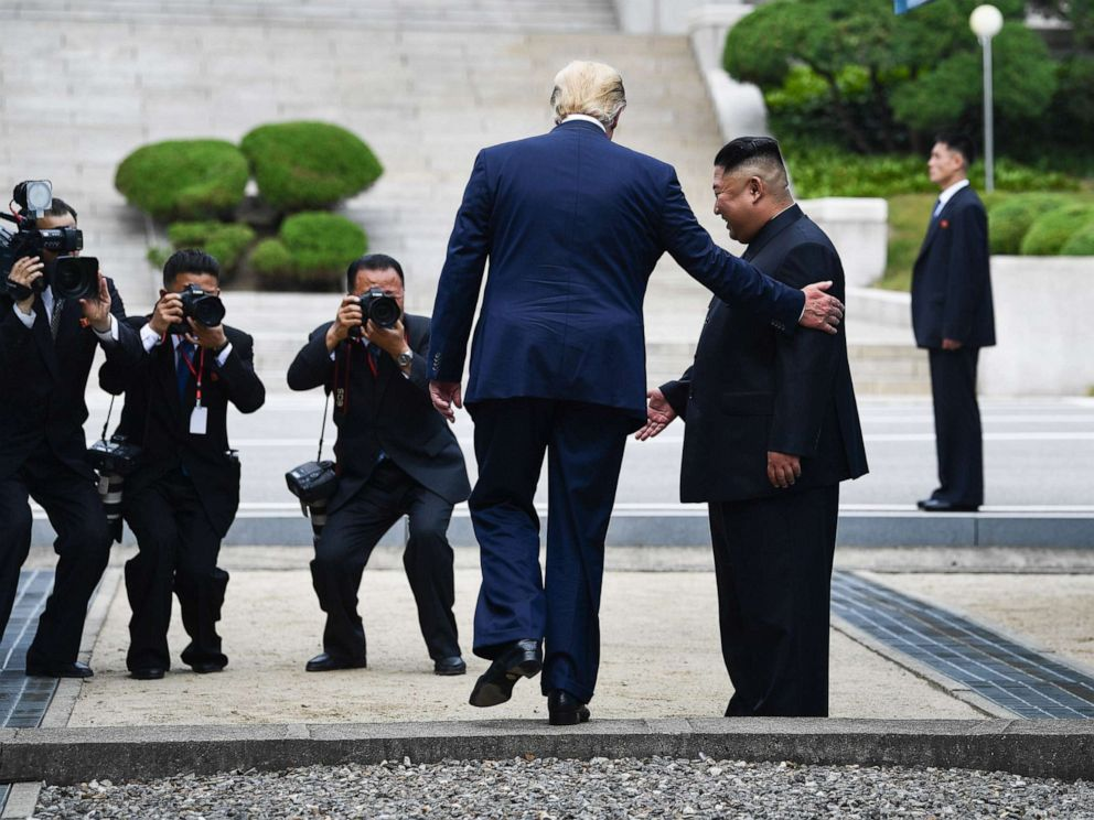 PHOTO: President Donald Trump steps into the northern side of the Military Demarcation Line that divides North and South Korea, as North Koreas leader Kim Jong Un looks on, in the Demilitarized zone (DMZ), June 30, 2019.