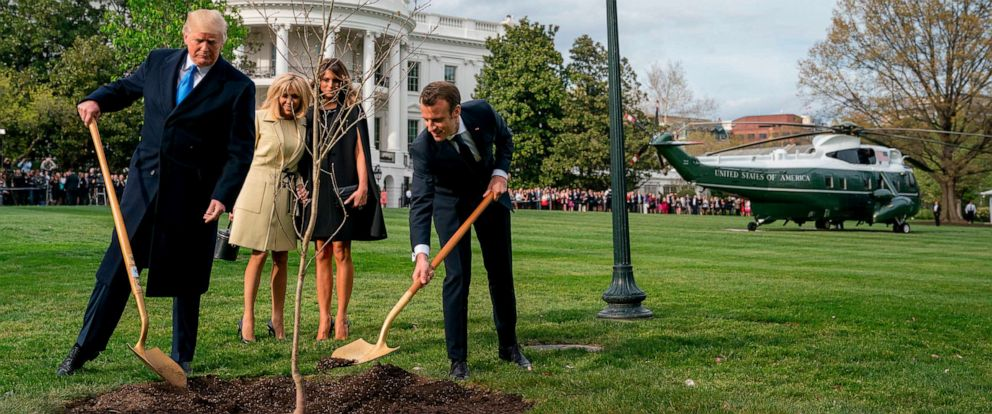 PHOTO: In this April 23, 2018, file photo, President Donald Trump and French President Emmanuel Macron participate in a tree planting ceremony on the South Lawn of the White House in Washington.