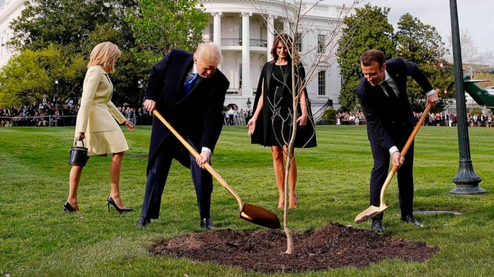President Donald Trump and French President Emmanuel Macron shovel dirt onto a freshly planted oak tree as first lady Melania Trump and Brigitte Macron watch on the South Lawn of the White House in Washington, D.C., April 23, 2018.