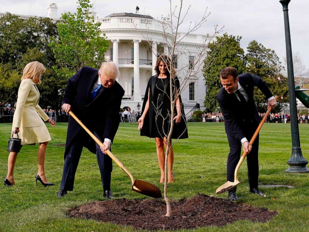 PHOTO: President Donald Trump and French President Emmanuel Macron shovel dirt onto a freshly planted oak tree as first lady Melania Trump and Brigitte Macron watch on the South Lawn of the White House in Washington, D.C., April 23, 2018.