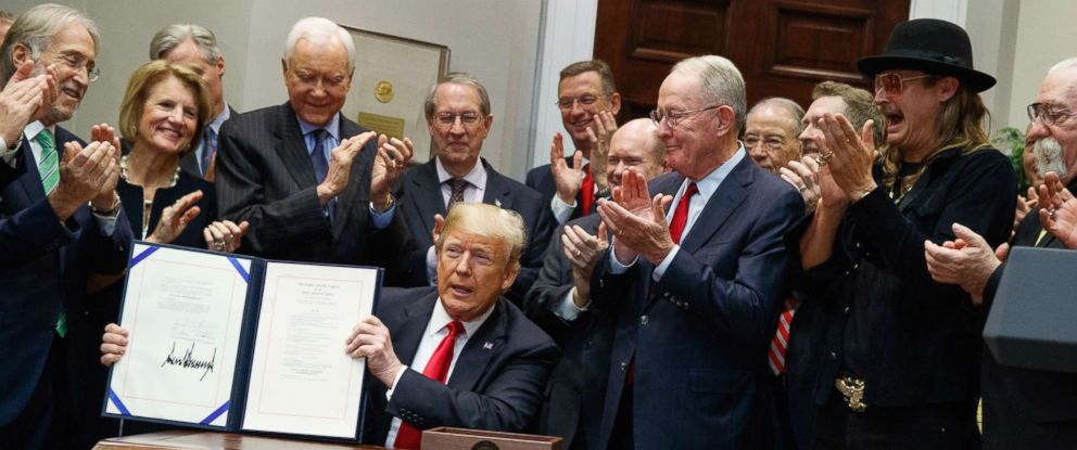 """PHOTO: President Donald Trump shows the """"Orrin G. Hatch-Bob Goodlatte Music Modernization Act,"""" after signing it in the Roosevelt Room of the White House, Oct. 11, 2018."""