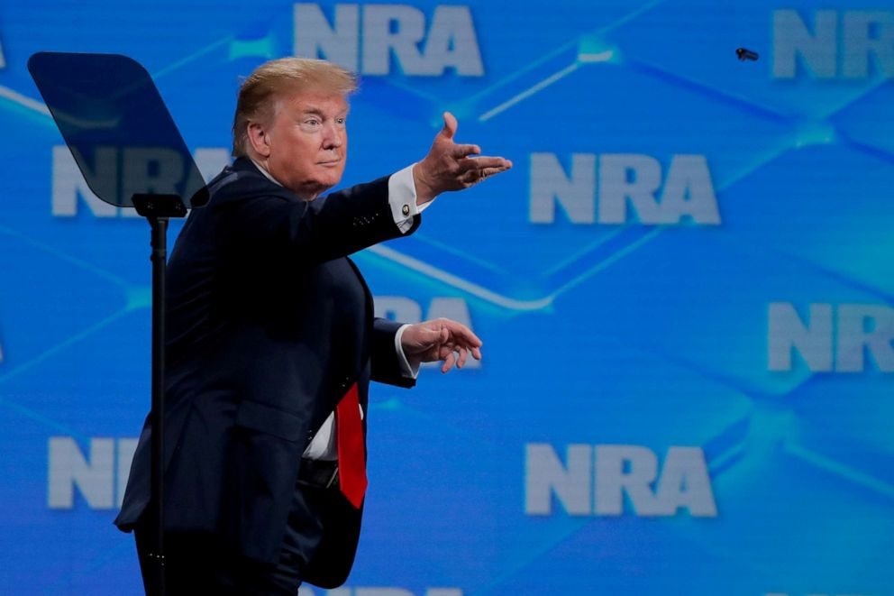 PHOTO: Donald Trump tosses a pen to the crowd after signing an executive order as he announces that the U.S. will drop out of the Arms Trade Treaty at the National Rifle Associations 148th annual meeting in Indianapolis, on April 26, 2019.