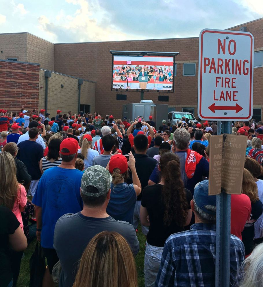 PHOTO: Hundreds of people in an outside overflow crowd watch President Donald Trump speak inside Olentangy Orange High School in Lewis Center, Ohio, Aug. 5, 2018.