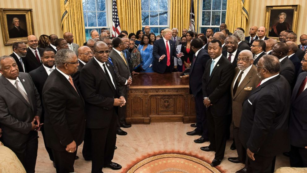 Omarosa Manigault (center R), communications director for the White House Office of Public Liaison, stands with President Donald Trump as he waits for a group photo with leaders of historically black universities and colleges in the Oval Office of the White House, Feb. 27, 2017 in Washington, D.C.