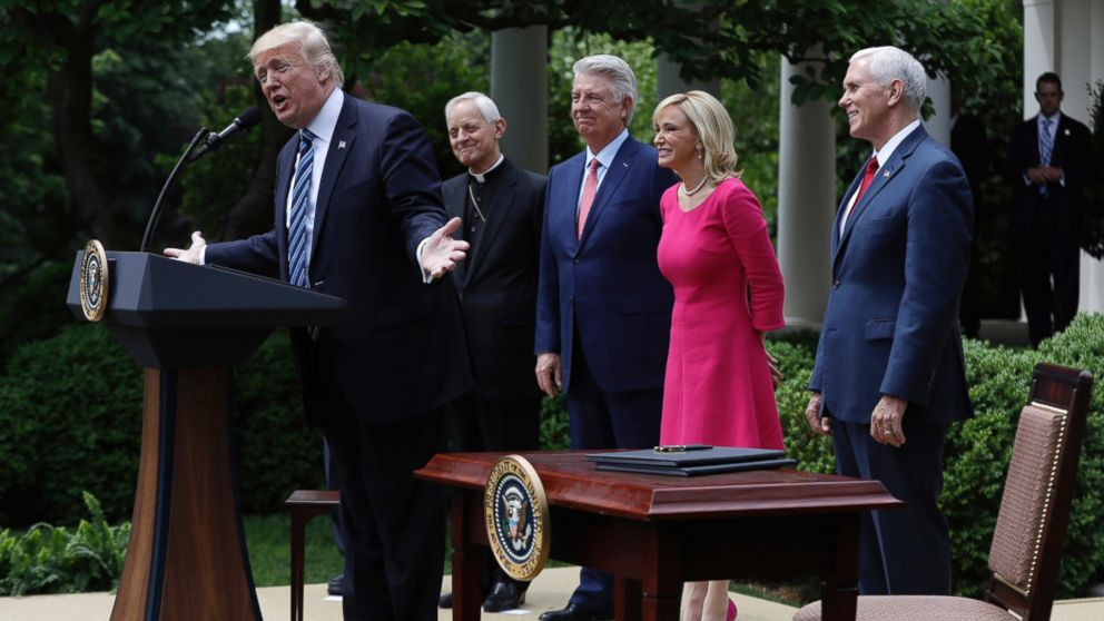 In this Thursday, May 4, 2017 file photo, President Donald Trump speaks in the Rose Garden of the White House in Washington, before signing an executive order aimed at easing an IRS rule limiting political activity for churches. From second from left are, Cardinal Donald Wuerl is the Archbishop of Washington, Pastor Jack Graham, Paula White, senior pastor of New Destiny Christian Center in Apopka, Fla. and Vice President Mike Pence.