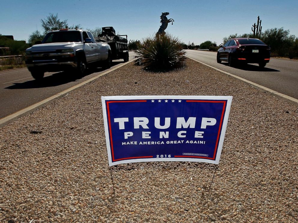 PHOTO: Motorist pass a campaign sign for Republican presidential candidate Donald Trump and vice presidential running mate Mike Pence posted in the center median of a roadway near a polling station on Nov. 8, 2016 in Cave Creek, Arizona.