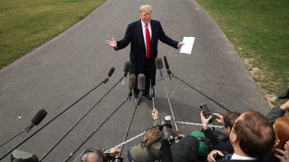 President Donald Trump talks with journalists before departing the White House March 20, 2019.