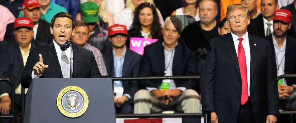 PHOTO: President Donald Trump listens to Rep. Ron DeSantis as he asks for the support of Trump voters in his bid to become Floridas next governor at a Make America Great Again Rally on July 31, 2018, in Tampa, Fla.
