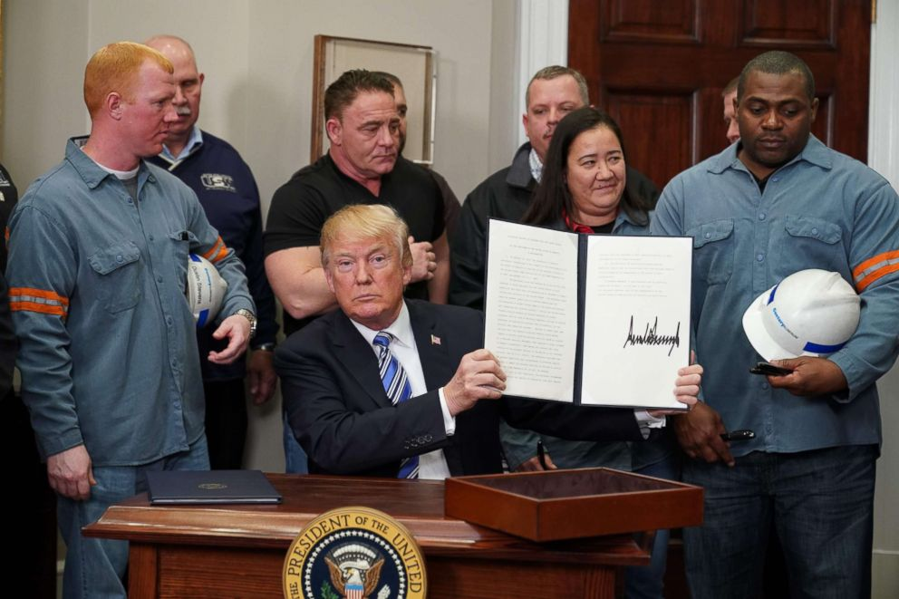 PHOTO: President Donald Trump signs Section 232 Proclamations on Steel and Aluminum Imports in the Oval Office of the White House, March 8, 2018, in Washington.