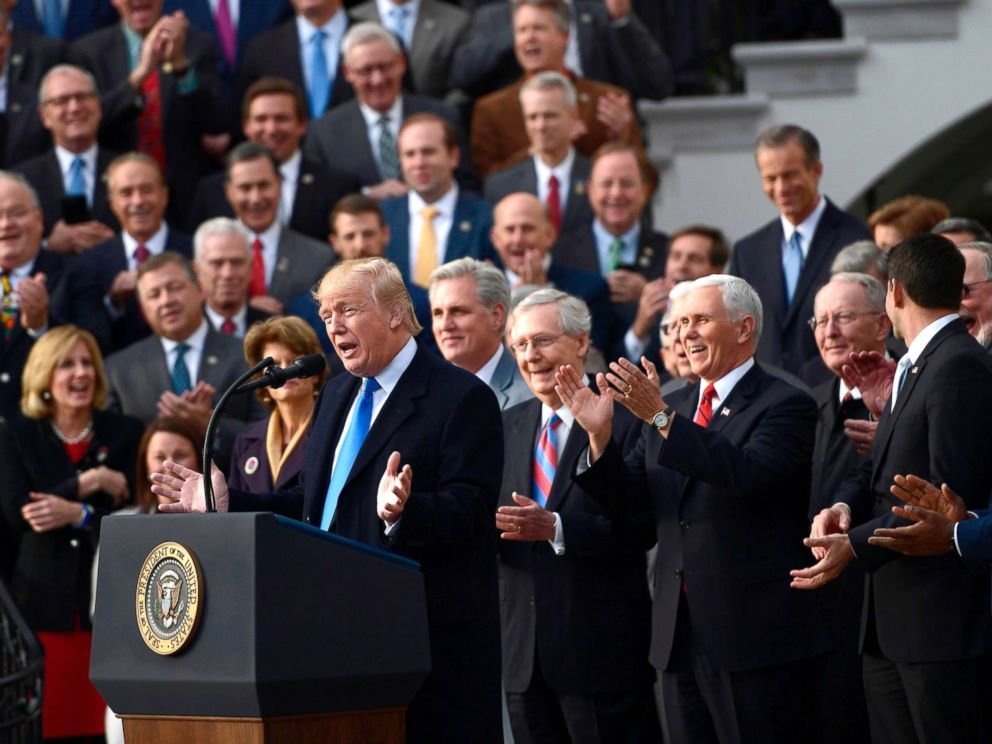 PHOTO: Surrounded by Republican Senators and House Representatives, President Donald Trump speaks about the passage of tax reform legislation on the South Lawn of the White House, December 20, 2017.