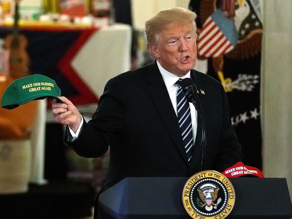 PHOTO: President Donald Trump holds up a Make Our Farmers Great Again hat as he speaks during the 2018 Made in America Product Showcase event July 23, 2018 at the White House in Washington.