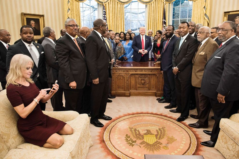 PHOTO: Counselor to the President Kellyanne Conway (L) checks her phone after taking a photo as President Donald Trump and leaders of historically black universities and colleges pose for a group photo in the Oval Office of the White House, Feb. 27, 2017.