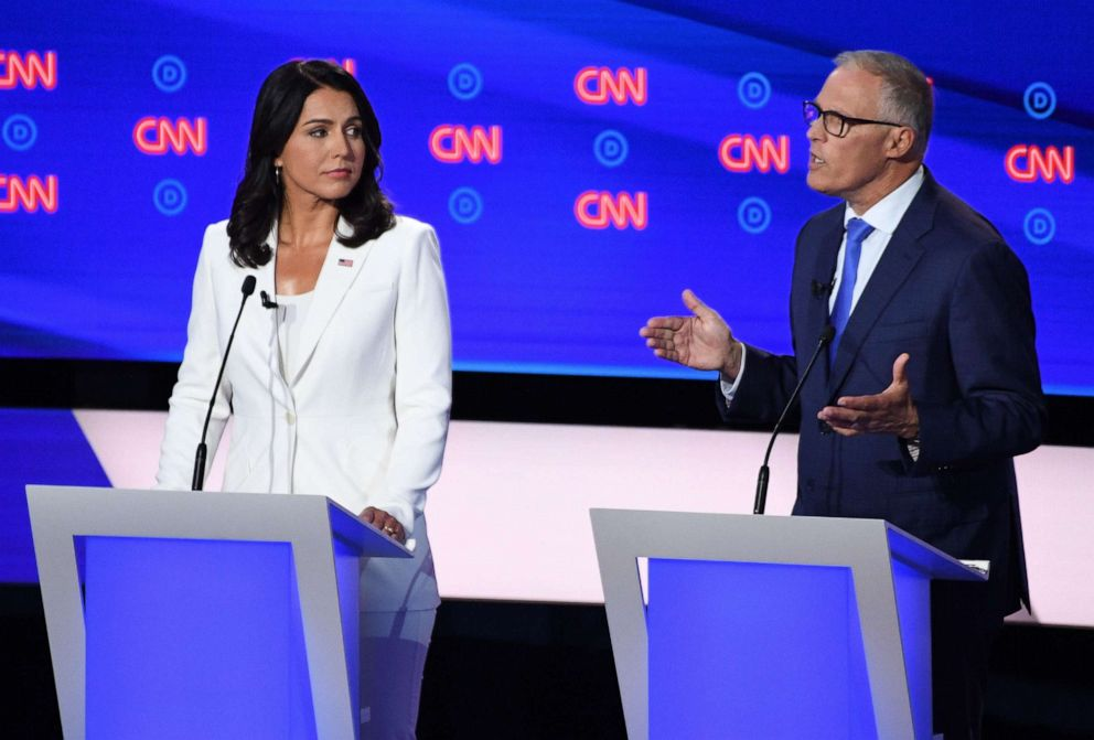 PHOTO: Democratic presidential hopefuls US Representative for Hawaiis 2nd congressional district Tulsi Gabbard (L) and Governor of Washington Jay Inslee (R) speak during the second round of the second Democratic primary debate.