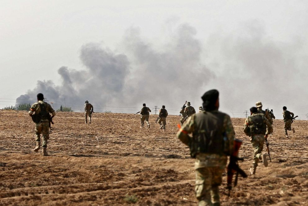 PHOTO: Pro-Turkish Syrian fighters cross the border into Syria as they take part in an offensive against Kurdish-controlled areas in northeastern Syria launched by the Turkish military, Oct. 11, 2019.