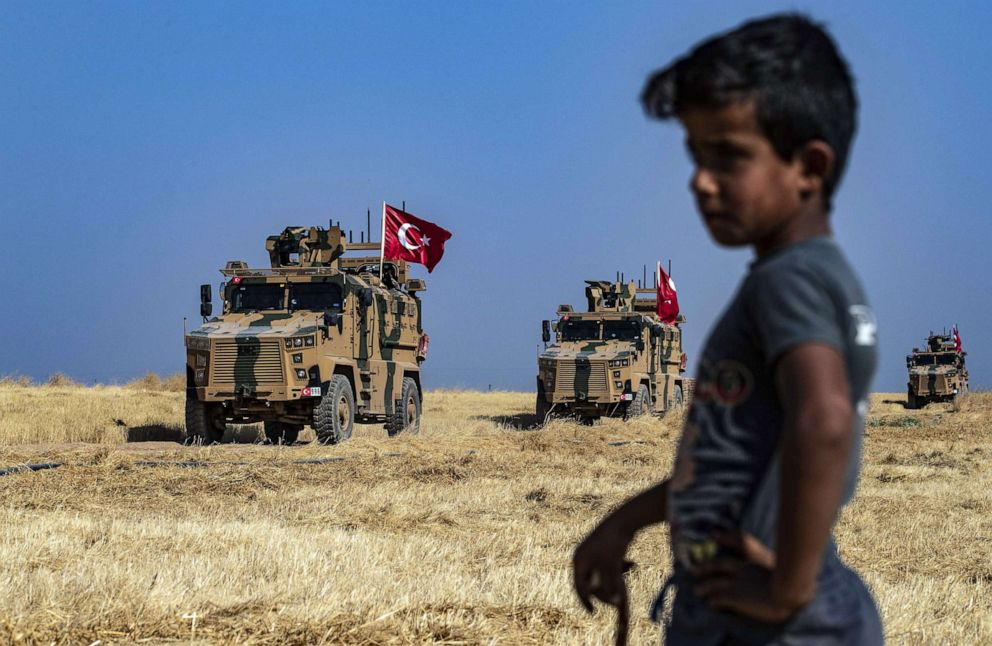 PHOTO: A Syrian boy watches as Turkish military vehicles, part of a U.S. military convoy, take part in joint patrol in the Syrian village of al-Hashisha along the border with Turkey, Oct. 4, 2019.