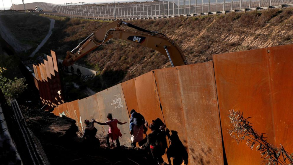 Migrants, part of a caravan of thousands from Central America trying to reach the U.S., climb down a steep hill after giving up on trying to climb the border wall into the U.S. from Tijuana, Mexico, Dec. 13, 2018.