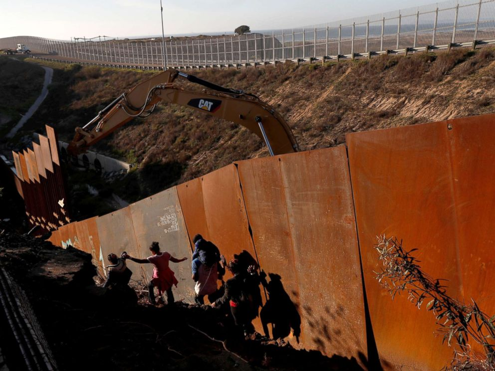 PHOTO: Migrants, part of a caravan of thousands from Central America trying to reach the U.S., climb down a steep hill after giving up on trying to climb the border wall into the U.S. from Tijuana, Mexico, Dec. 13, 2018.