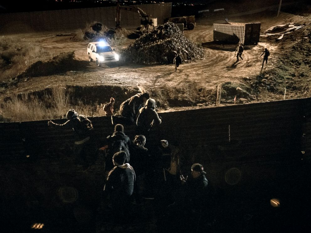 PHOTO: A border patrol officer is overpassed by migrants running away after climbing the border fence, while others jump inside the United States to San Diego from Tijuana, Mexico, Dec. 25, 2018.