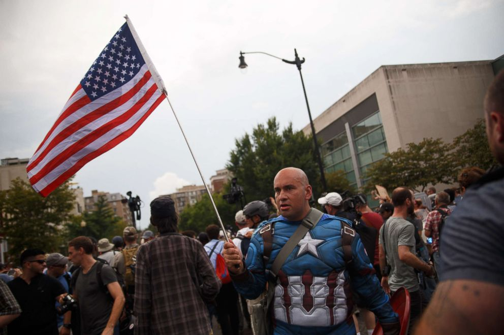 PHOTO: A counterprotester dressed as Captain America taunts white supremacists, escorted by police, who are making their way from Foggy Bottom Metro station to Lafayette Park for a Unite the Right event on Aug. 12, 2018, in Washington, D.C.