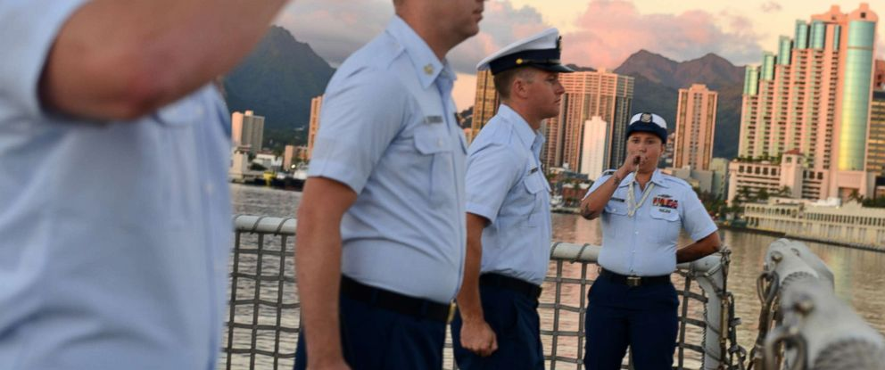 PHOTO: Petty Officer 3rd Class Bianca Valenzuela pipes colors using a boatswains pipe during a ceremony aboard the Coast Guard Cutter Sherman the evening before the cutter is scheduled to be decommissioned in Honolulu, Mar. 28, 2018.