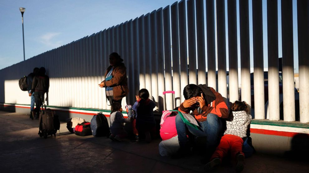 A migrant sits with his children as they wait to hear if their number is called to apply for asylum in the United States, Jan. 25, 2019, in Tijuana, Mexico.