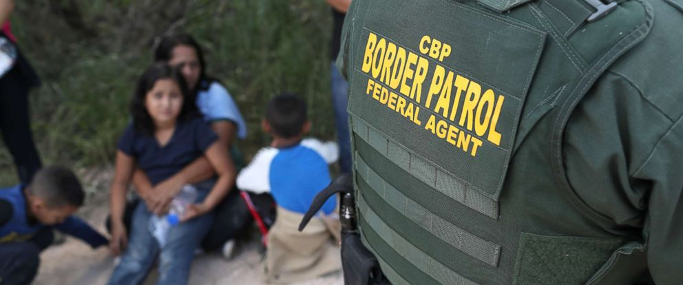PHOTO: Central American asylum seekers wait as U.S. Border Patrol agents take them into custody on June 12, 2018 near McAllen, Texas.