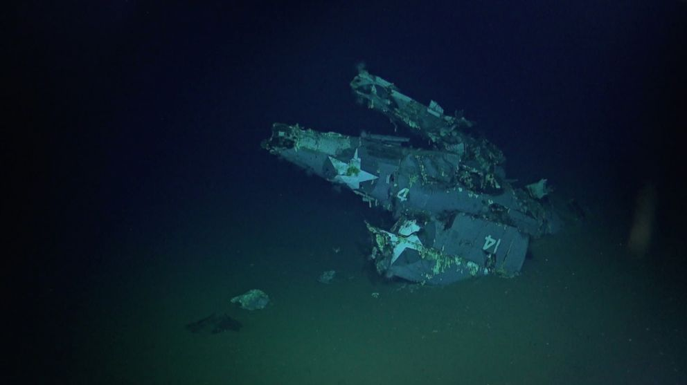 An F4F-4 Wildcat fighter aircraft with its wings folded sits on the ocean floor.
